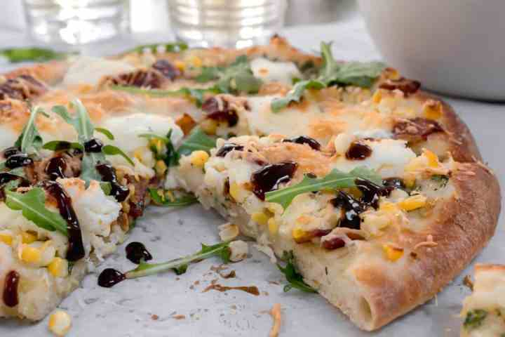 slice of sweet corn and bacon pizza with balsamic glaze