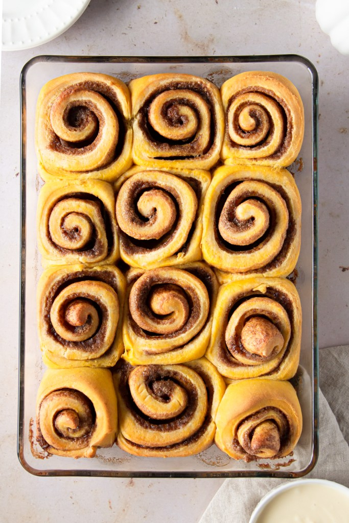 twelve pumpkin spice rolls in a baking dish