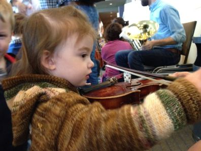 Audrey tries out a violin from a member of the Seattle Symphony Soundbridge program.