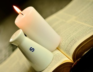 Salt shaker and candle on top of an opened Bible