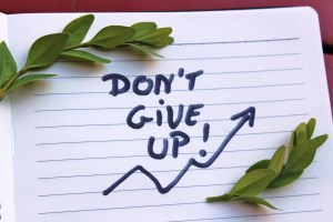 """""""Don't Give Up!"""" written on a notepad"""