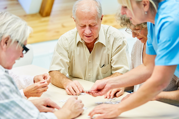 Group of seniors with dementia and caregiver playing with puzzle in retirement home
