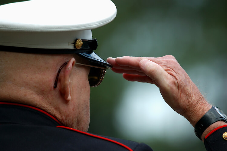 An elderly, retired marine salutes during a ceremony honoring veterans.