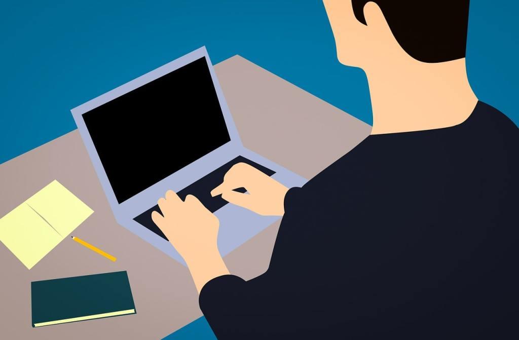 Homme qui blogge sur son ordinateur