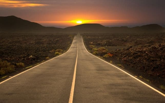 Go! Open road driving into sunset