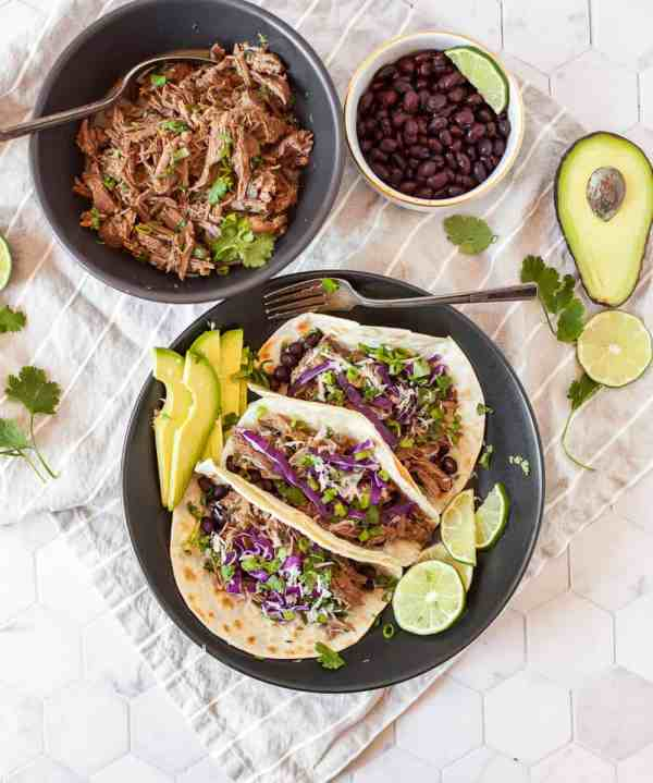 Our Instant Pot Shredded Beef Tacos are perfect for Taco Tuesdays or meal prep on Sundays! This simple shredded beef cooks up juicy and flavorful in the pressure cooker and can be used for many recipes besides tacos. | MarathonHandbook.com #instantpot #pressurecooker #beef #tacos