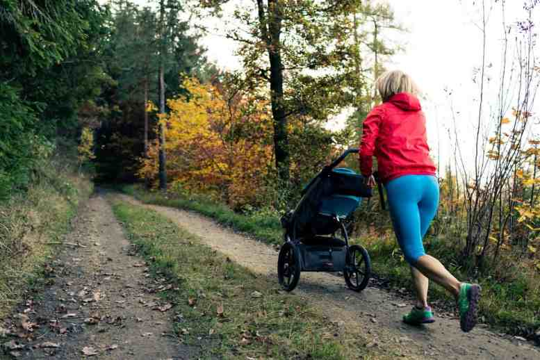 woman jogging with a stroller on a wooded trail - tips on postpartum running