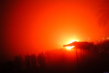 ...the fire burnishes blindingly, momentarily setting the smoke-filled night sky ablaze with startling red hues.
