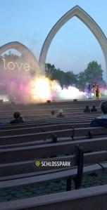 Man sieht große Nebelschwaden, die mit vielen Farben angeleuchtet sind. Am Rande steht ein Schauspieler in einem bunten Kostüm. Darüber sind die Torbögen des Freilichttheaters.