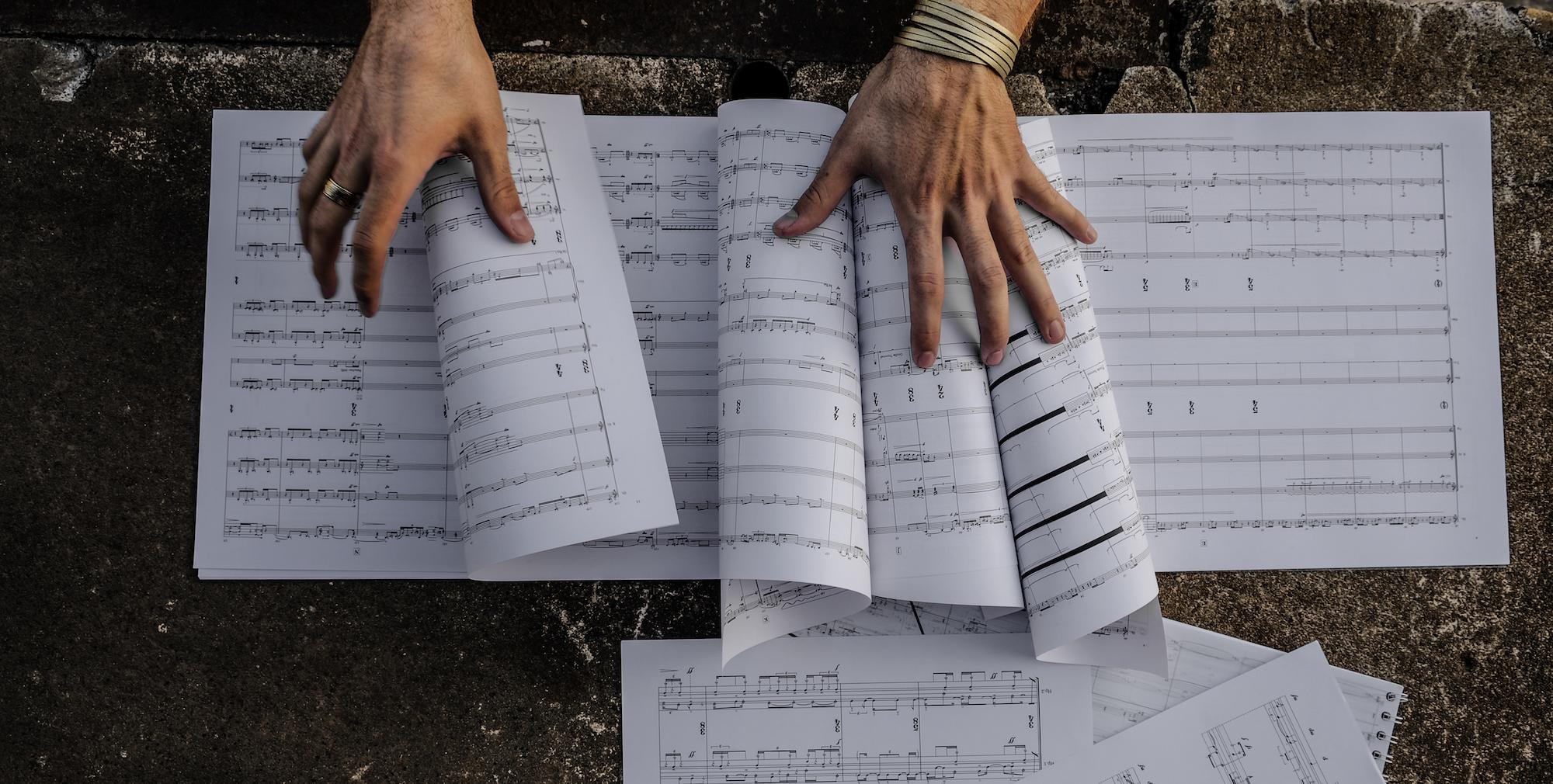 {:de}Komponist Marc David Ferrum Hände über seiner Partitur{:}{:en}Composer Marc David Ferrum Hands over his score{:}