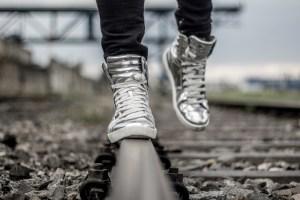 Komponist Marc David Ferrum silberne Schuhe auf Gleisen