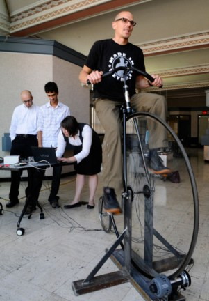 Waterloo, Ontario - Wednesday Aug 5, 2009Marcel O'Gorman sits on a penny farthing bicycle in a workspace near city hall in Kitchener, Wednesday. The bike will be hardwired to a computer so that a pedalist's speed and heart rate control an animation projected onto the walkway between GoodLife and Delta over King Street. Mathew McCarthy, Record staff - see story by Colin Hunter. Request #-Local Arts_4:25:56 PM-05/08/09-Waterloo