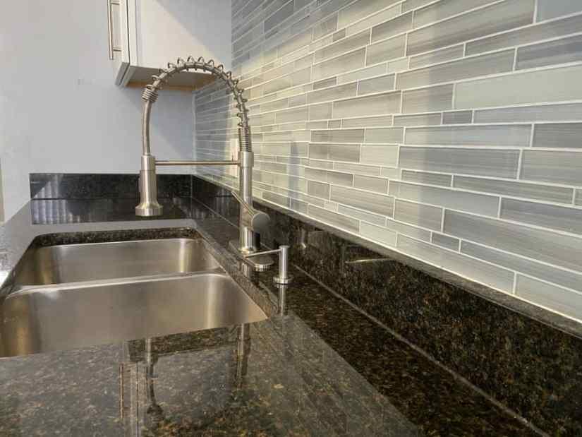 blue mosaic glass tile backsplash against black granite countertop