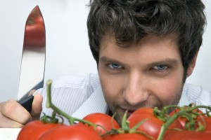 700-02756603 © Siephoto Model Release: Yes Property Release: No Man With Knife and Tomatoes