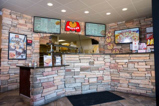 The stone-tiled interior counter at a Marco's Pizza, with televisions displaying the menu behind it.