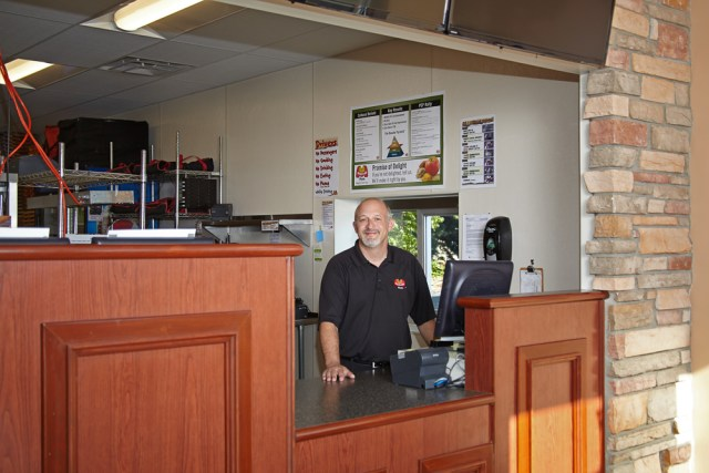 A franchisee poses behind the register at a Marco's Pizza location.