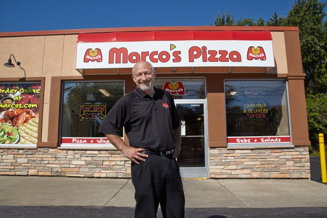 A Marco's franchisee poses in front of his location.