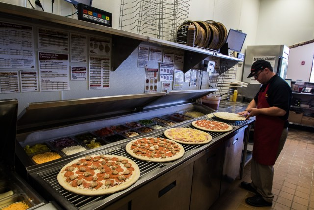 A Marco's Pizza franchisee prepares five pizzas, including two sausage-and-pepperoni, one pepperoni, one Hawaiian and one cheese, in the back area of his location.