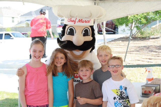 A Chef Marco® mascot poses with five smiling children at a catered outdoor event.