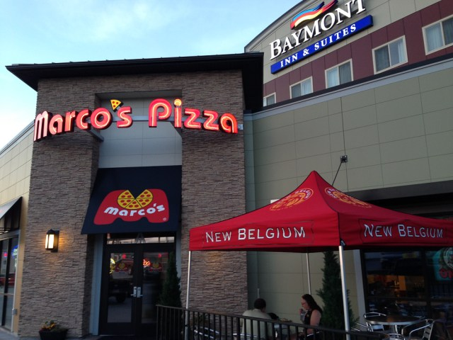 The exterior of a Marco's Pizza located at a Baymont Inn & Suites. Two guests enjoy a meal on the patio under a New Belgium-branded tent.
