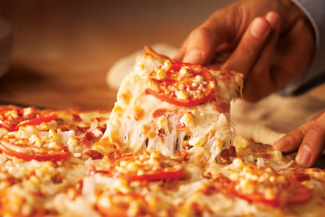 A hand removes a slice from one of our White Cheezy specialty pizzas.