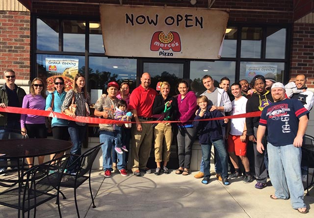 Community members are gathered around at a ribbon cutting for a new Marco's Pizza franchise location.