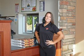 Marco's Pizza franchisee Ashley Jones stands in front of the counter at one of her restaurants, with a stack of three pizza boxes on the counter next to her.