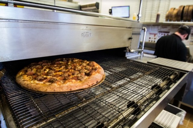 A fresh pizza covered in sausage and pepperoni rolls out of a conveyor belt oven.