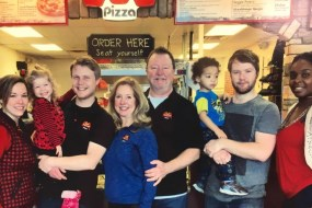Brian Fairbanks (third from left) poses with his family at their Marco's Pizza franchise.