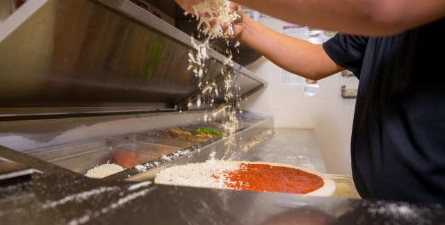 A Marco's Pizza franchise employee sprinkles fresh cheese on sauce-covered pizza dough on a stainless steel prep table in the back of a restaurant.