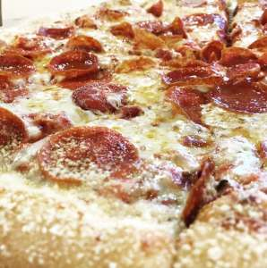 A close-up shot of a Pepperoni Magnifico pizza dusted with Parmesan cheese.