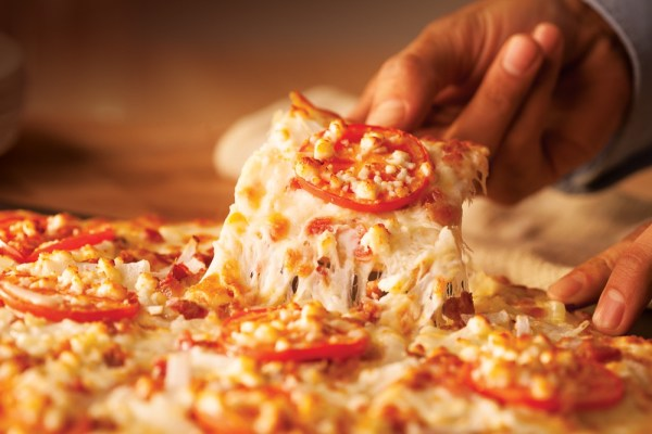 A hand lifts a slice of pizza covered in tomato slices and crumbled cheese.