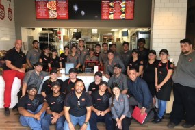 A Marco's Pizza franchisee and his team pose in front of the counter at a Marco's restaurant.