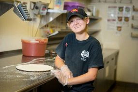 A Marco's Pizza franchise employee smiles for the camera while standing next to fresh pizza dough in the prep area of the restaurant.