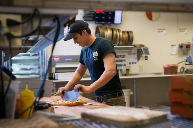 A candid photo of a smiling Marco's Pizza franchise employee slicing a pizza on a wooden table in the prep area of the restaurant.