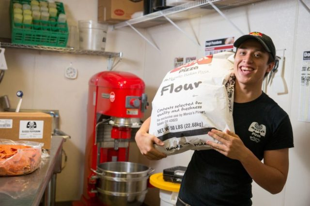 A smiling Marco's Pizza franchise employee hoists a large bag of flour over his shoulder in the prep area of a restaurant.