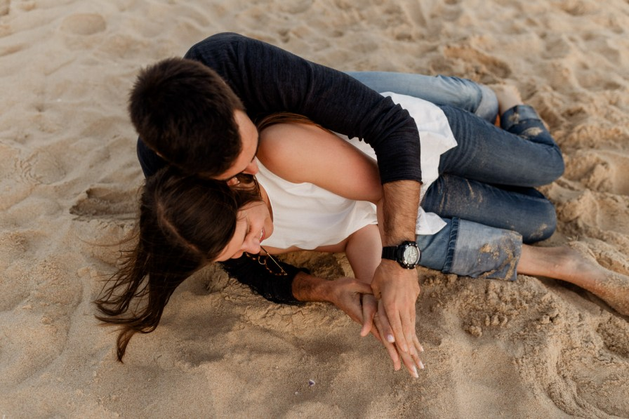 young couple rolling in the sand at a engagement session
