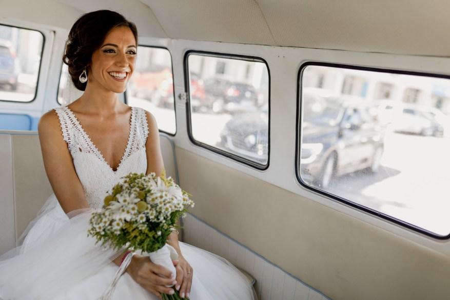 noiva sorrindo dentro da carrinha vw da kombimania a caminho da cerimónia