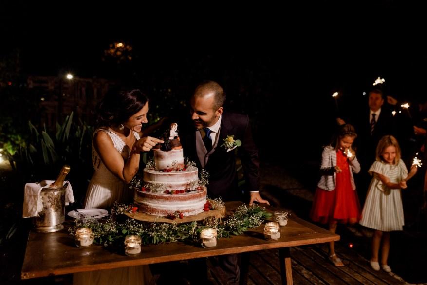 noivos vêm topo do bolo feito pela love in wire no jardim da quinta espaço caiado, na sobreda