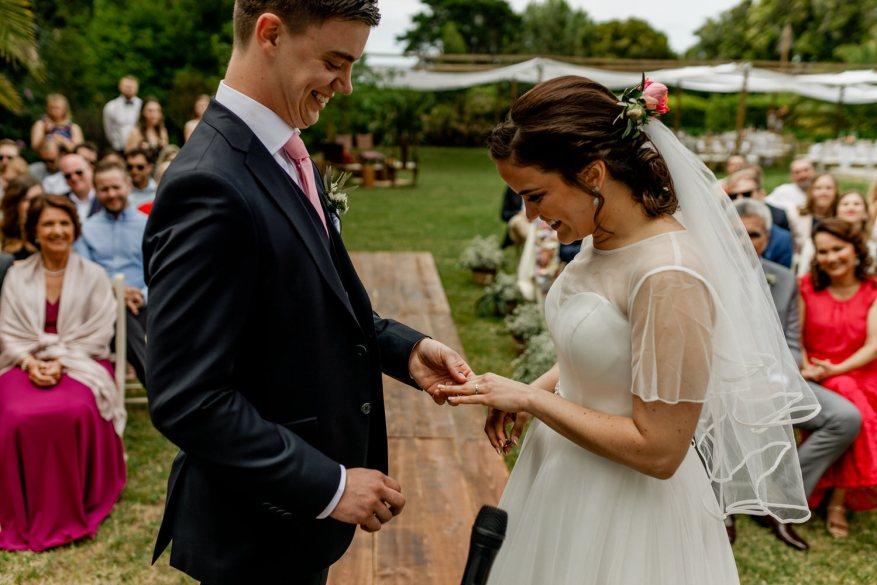 noivo mete a aliança no dedo da noiva