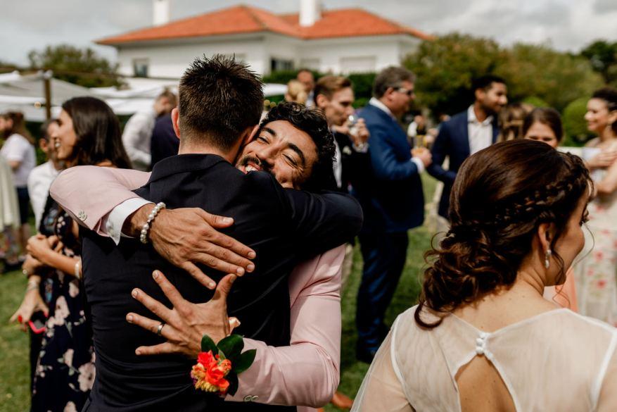 abraço emocional entre o noivo e um damo de honor