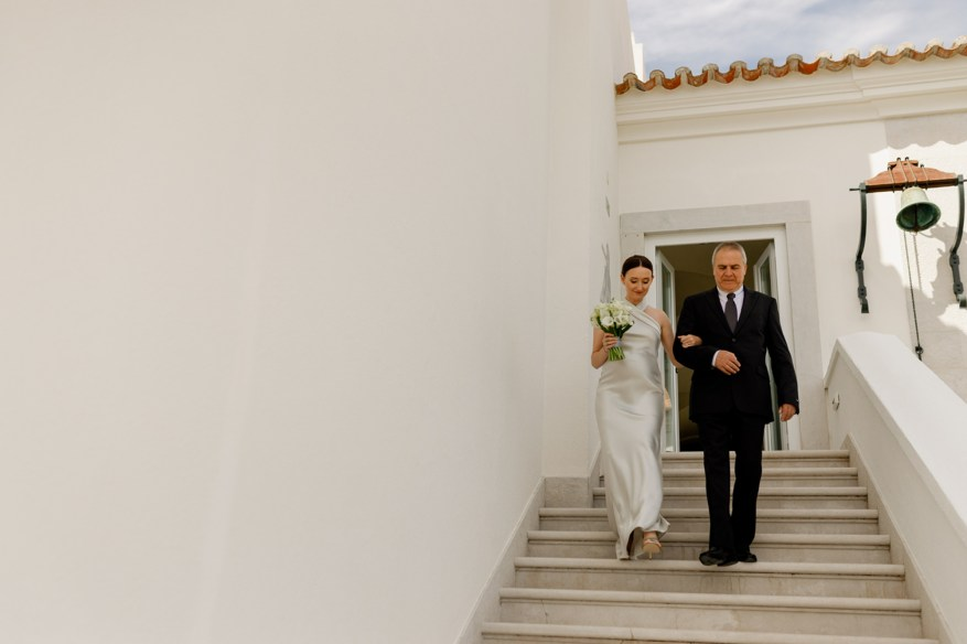 bride walks down the stairs with her father