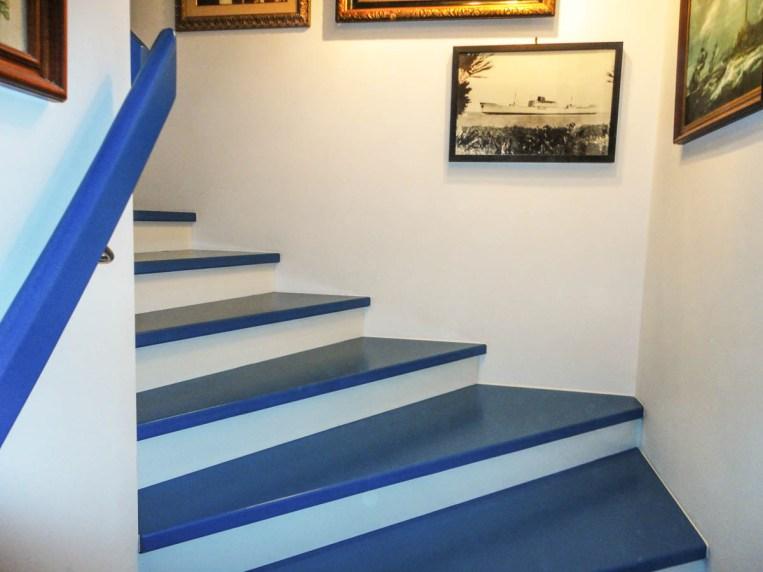 Azurblaue Trittstufen und gleichfarbiger Wandhandlauf, mit weißen Setzstufen