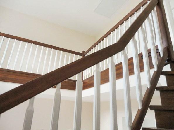 Dunkel gebeizte Stufenverkleidung in Kombination mit weißen Holzsprossen
