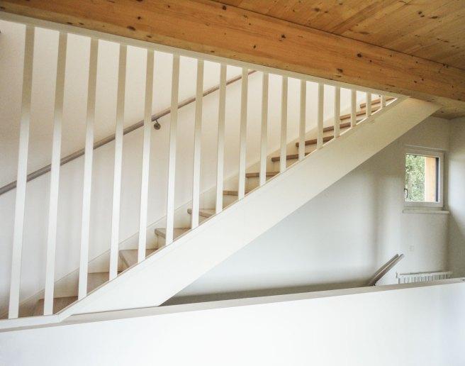 Geschlossene Treppe aus Eichenholz mit weiß lasierten Trittstufen, deckend weiß lackierten Wangen und Geländer