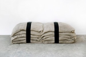 Marcus Kleinfeld, DIALECTICS, 2010 Hand-painted hessian sacks, sand, black funeral ribbon Dimensions variable