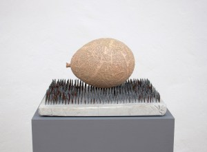 Sculpture by artist Marcus Kleinfeld titled 'Forces', depicting a paper maché balloon on top of cast nails