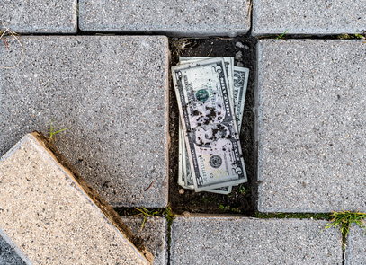 US dollar banknotes found under a loose pavement brick