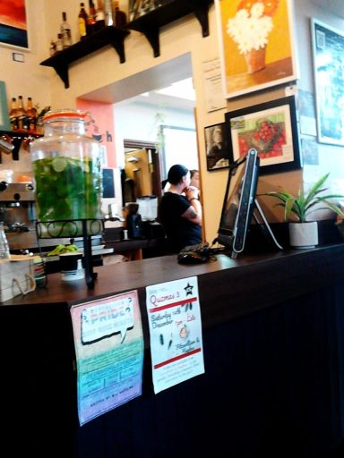 A photo of counter, the till and my  painting of apples in the  cafe