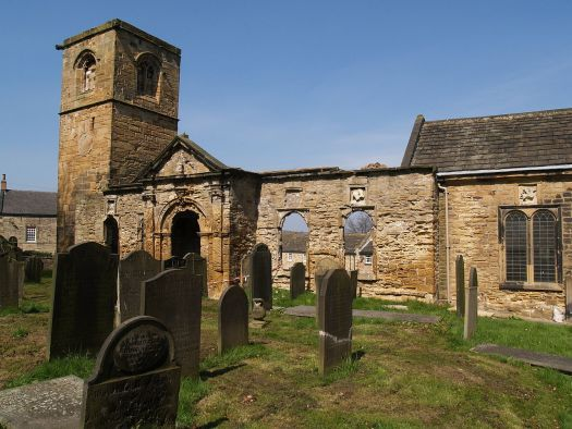 A sunlit photo of the ruined building and the gravestones in the churchyard.
